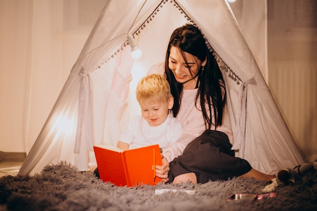 Madre con hijo sentado en una acogedora carpa con luces en casa en navidad Foto gratis