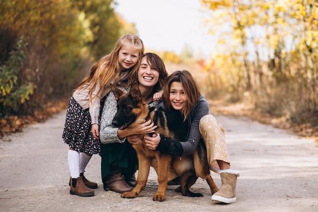 Madre con hijos y perro en un parque de otoño Foto gratis