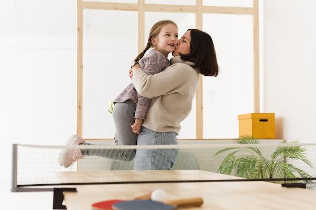 Madre levantando linda hija en el interior Foto gratis