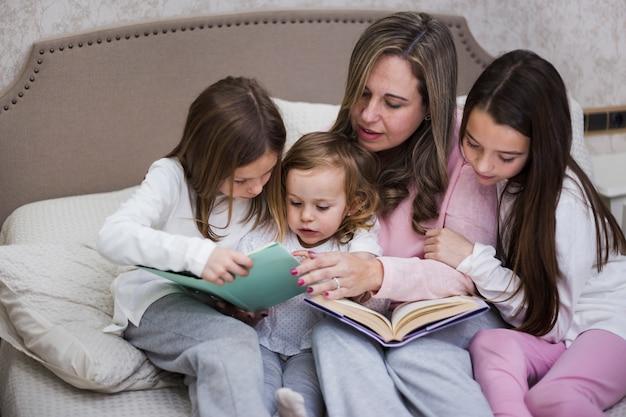 Madre leyendo junto con hijas Foto gratis