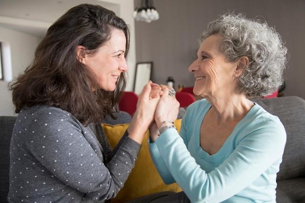 Madre mayor alegre y su hija que llevan a cabo las manos Foto gratis