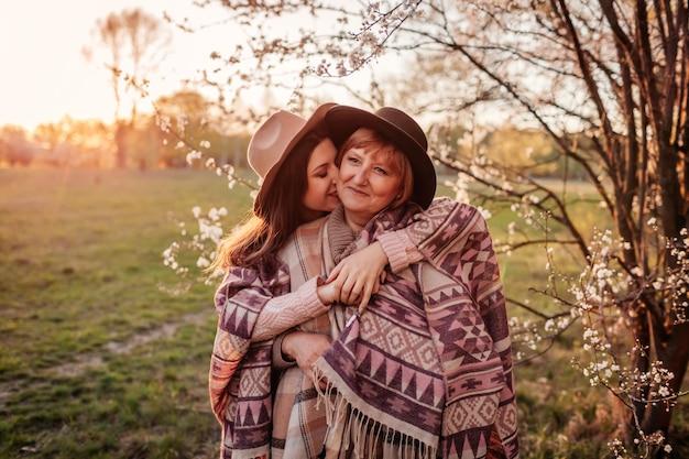 Madre de mediana edad y su hija adulta que abrazan en jardín floreciente. concepto del día de la madre. valores familiares Foto Premium