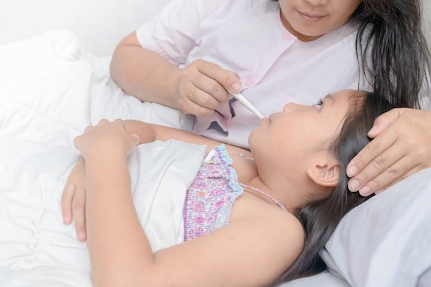 Madre midiendo la temperatura del niño enfermo. Foto Premium