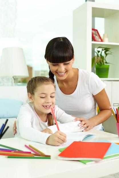 Madre mirando a su hija dibujando Foto gratis