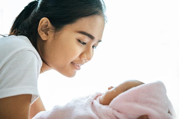 La madre miró al bebé que yacía en las manos de la madre. Foto gratis
