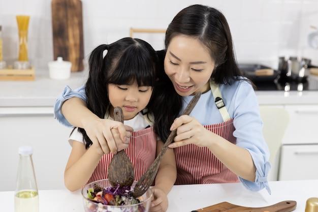 Madre y niña preparan la ensalada en un bol Foto Premium