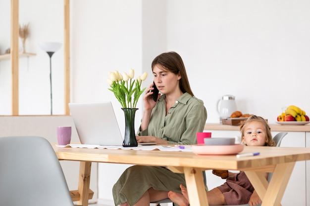 Madre y niña sentada en la mesa Foto gratis