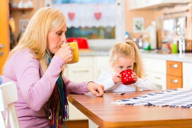 Madre y niño bebiendo leche en la cocina Foto Premium