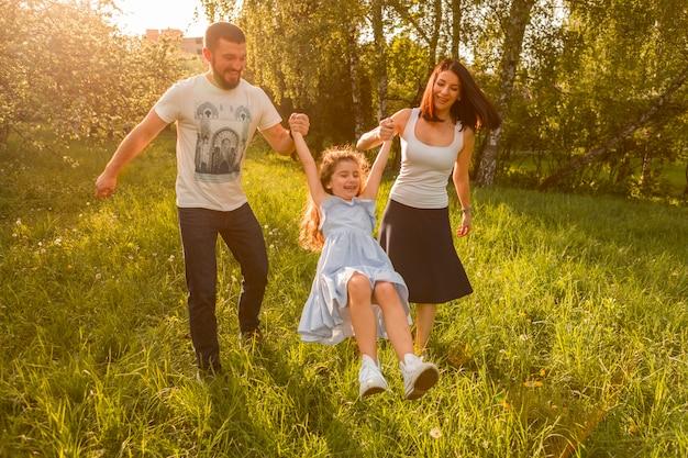 Madre y padre balanceando a su hija entre ellos Foto gratis