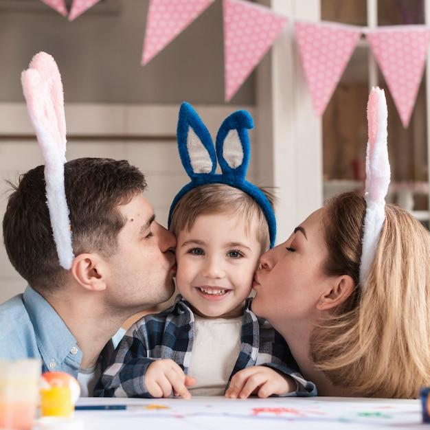 Madre y padre besándose adorable niño pequeño Foto gratis