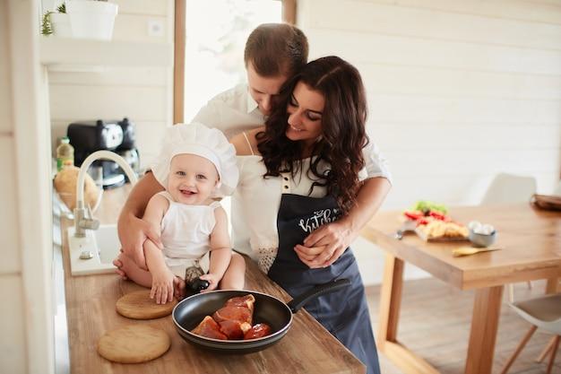 La madre, el padre y el hijo cocinando una carne Foto gratis
