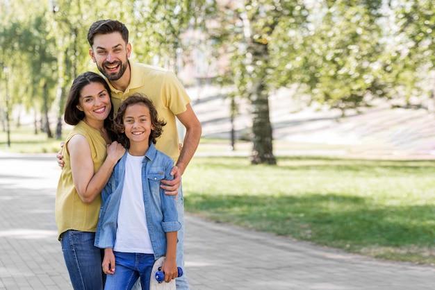 Madre y padre posando con su hijo en el parque. Foto gratis