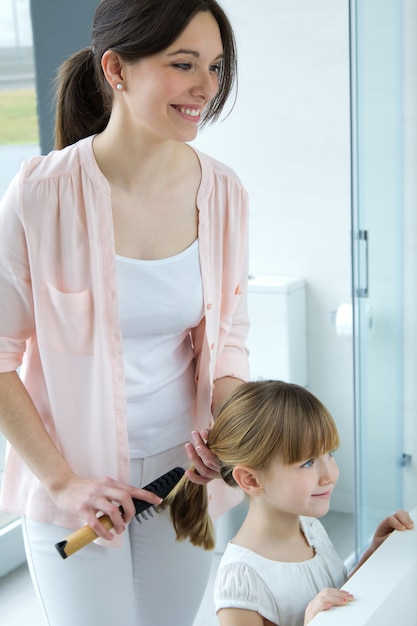Madre peinando a su hija en el cuarto de baño | Descargar ...