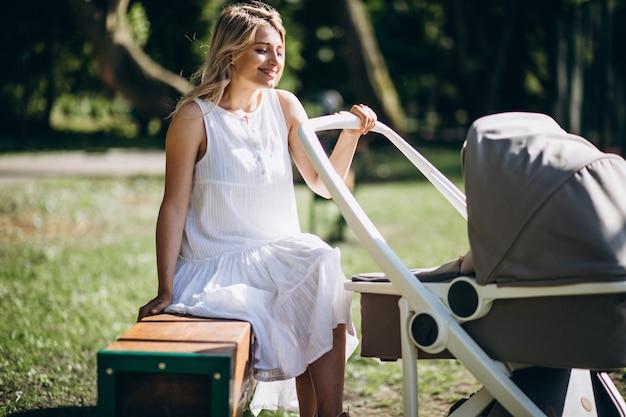 Madre con pequeña hija en el parque sentado en un banco Foto gratis