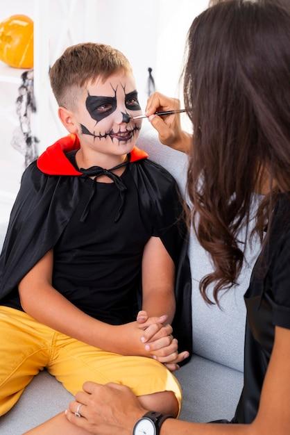 Madre pintando la cara de sus hijos para halloween Foto gratis