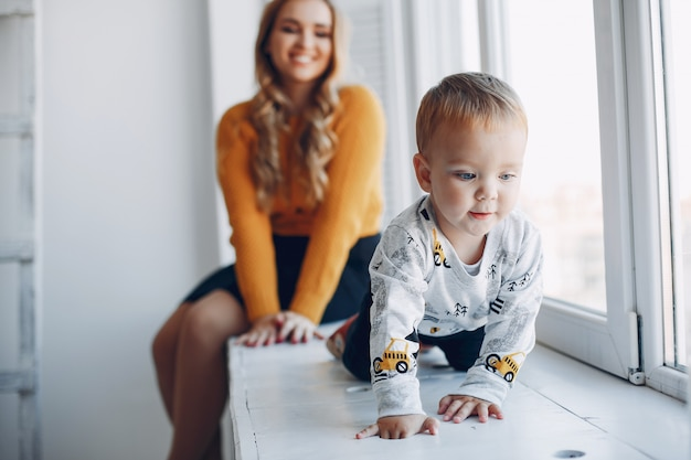 Madre sentada en casa con su pequeño hijo Foto gratis