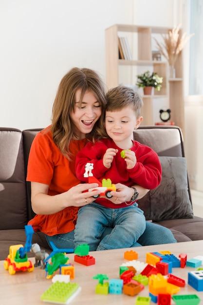 Madre sonriente jugando con su hijo Foto gratis