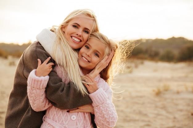 Madre sonriente jugando con su pequeña hija Foto gratis