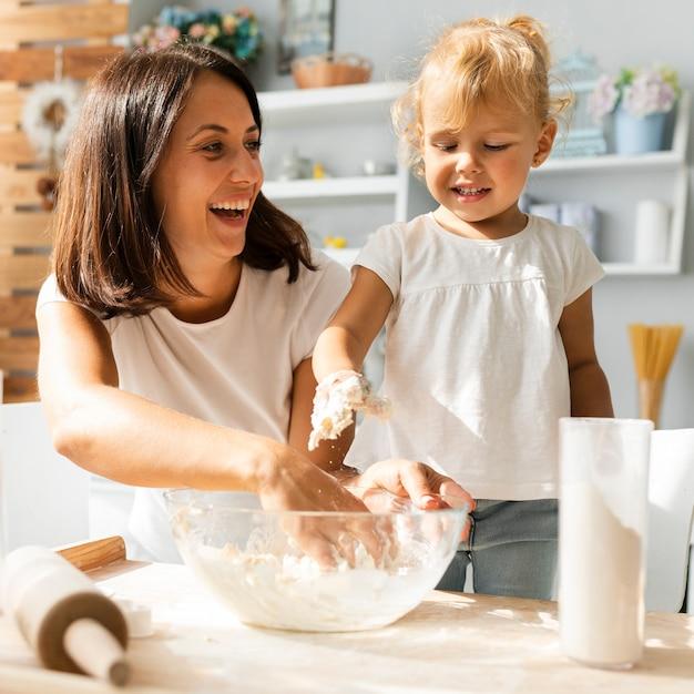 Madre sonriente y linda hija preparando masa Foto gratis