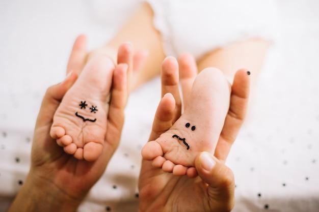 Madre sosteniendo los pies del bebé con emoticones Foto Gratis