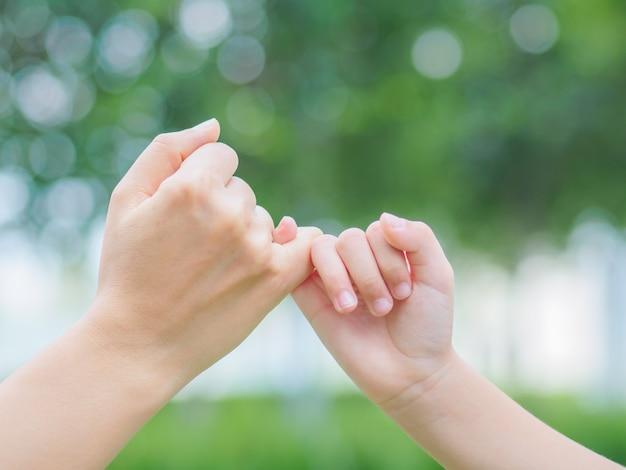 Madre sosteniendo una mano de su hijo al aire libre con fondo de campo verde Foto Premium