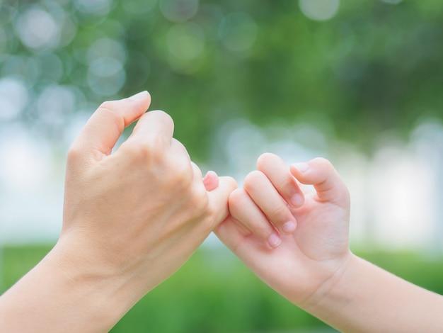 Madre sosteniendo una mano de su hijo en primavera al aire libre con fondo de campo verde Foto Premium