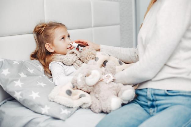 Madre con su hija illnes en un dormitorio Foto gratis