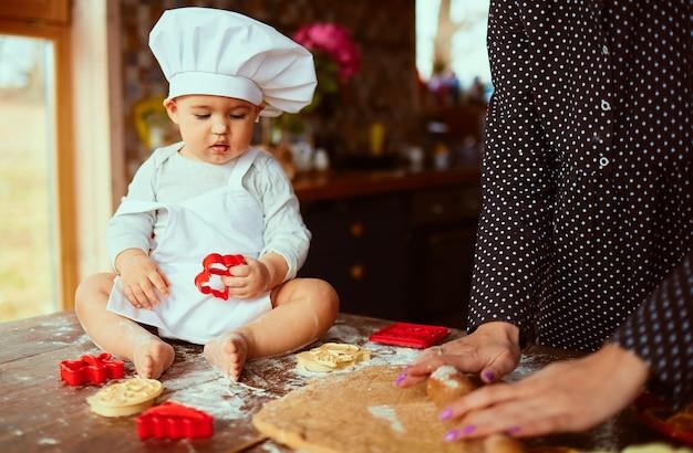 La madre con su hijo amasa la masa en la cocina Foto gratis