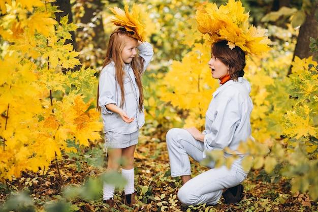 Madre con su pequeña hija en un bosque lleno de hojas doradas Foto gratis