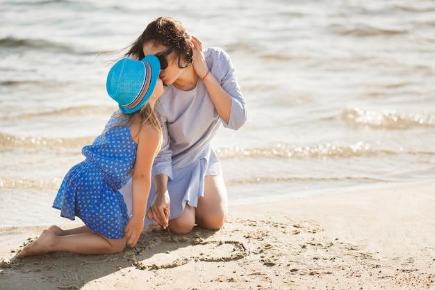 Madre y su pequeña hija divirtiéndose en la costa. joven madre bonita y su hijo jugando cerca del agua y dibujando un corazón en la arena Foto Premium