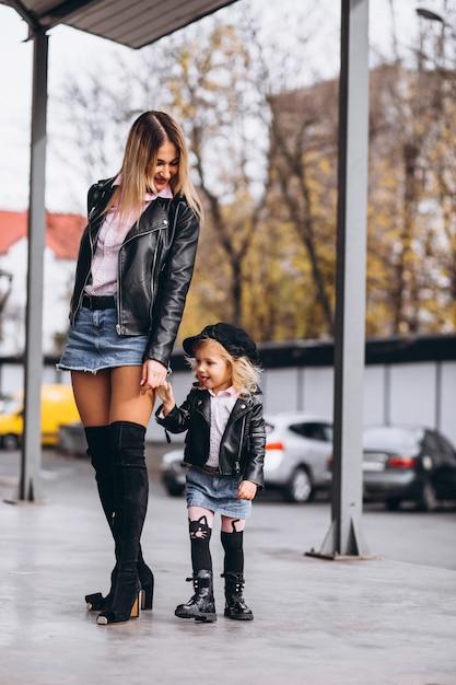 Madre con su pequeña hija fuera de la calle Foto gratis
