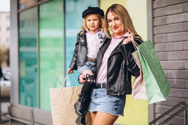 Madre con su pequeña hija linda con bolsas de compras Foto gratis