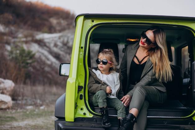 Madre con su pequeña hija sentada en la parte trasera del auto Foto gratis