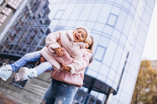Madre con su pequeña hija vestida con ropa de abrigo fuera de la calle Foto gratis