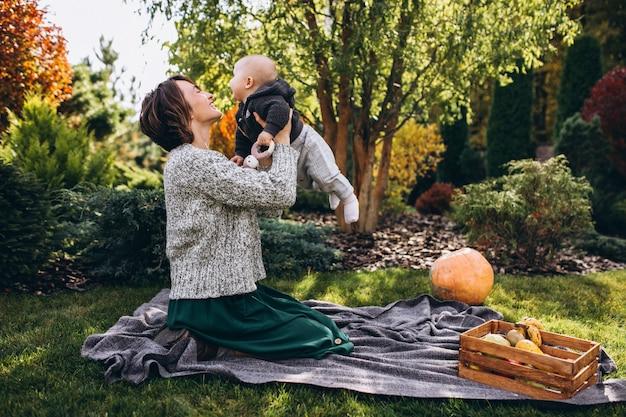 Madre con su pequeño hijo haciendo picnic en un patio trasero Foto gratis