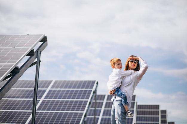 Madre con su pequeño hijo por paneles solares Foto gratis
