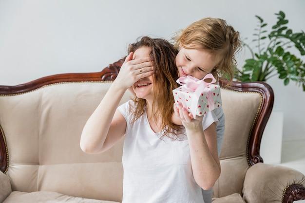 Madre tapándose los ojos mientras recibe el regalo del día de la madre en casa. Foto gratis