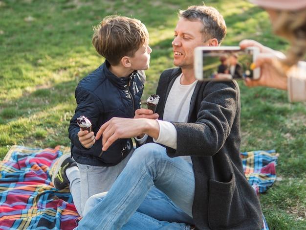 Madre tomando una foto de padre e hijo Foto gratis