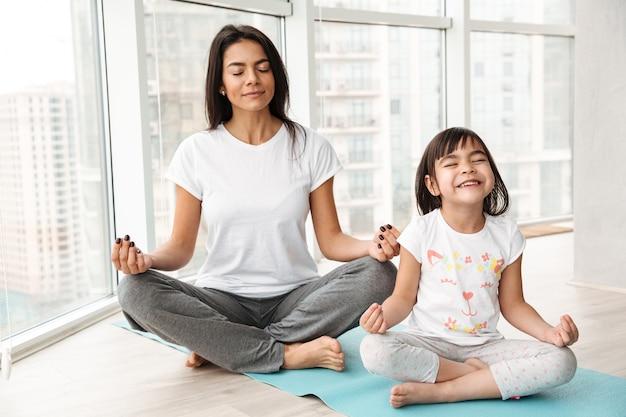 Madre tranquila y niña meditando en casa, sentada en postura de loto sobre estera y haciendo yoga mudra gesto con los dedos Foto Premium
