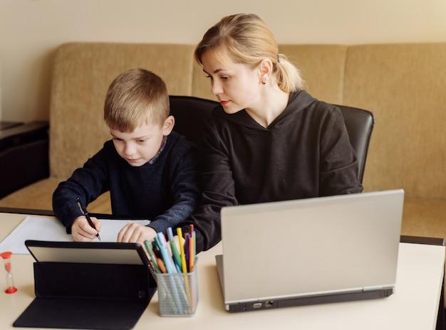 Madre usando una computadora portátil y una tableta enseñando con su hijo en línea en su casa en su habitación Foto gratis