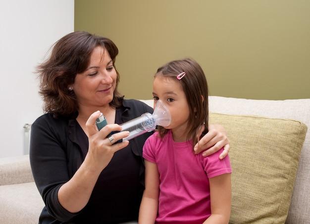 Madre usando inhalador con su hija asmática Foto Premium