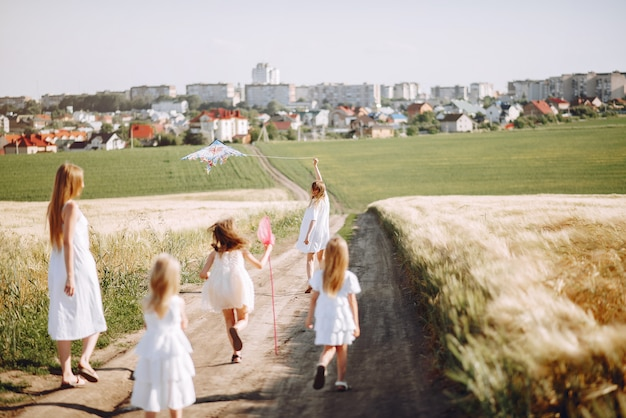 Madres con hijas jugando en un campo de otoño Foto gratis