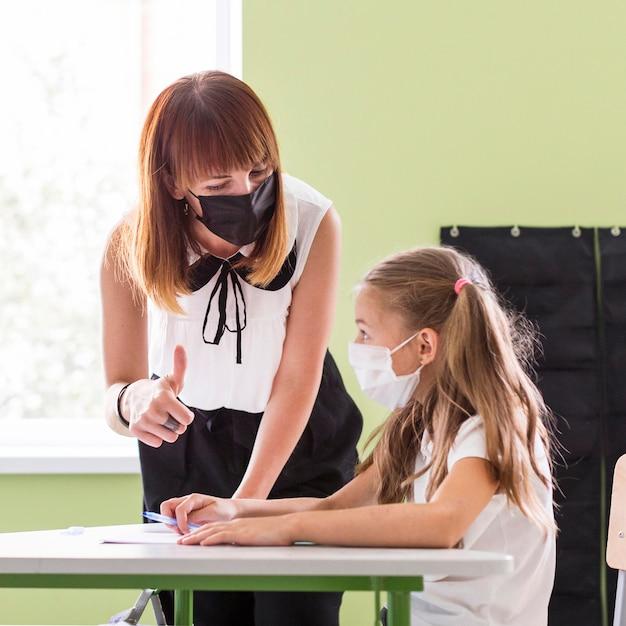 Maestra ayudando a su alumno en clase Foto gratis