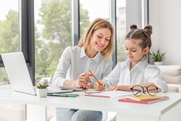 Maestra ayudando a su hija a estudiar en casa Foto gratis