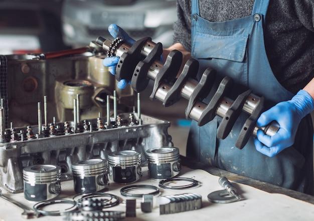 El maestro recoge un motor reconstruido para el automóvil. Foto Premium