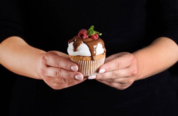 Magdalena con crema blanca regada con chocolate, raspada con frambuesas y menta en manos de un pastelero. Foto Premium