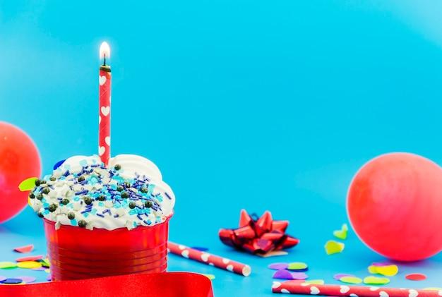 Magdalena de cumpleaños con una vela y globos Foto gratis