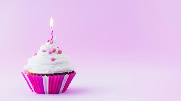 Magdalena del cumpleaños con la vela iluminada en fondo púrpura Foto Premium