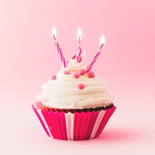 Magdalena fresca del cumpleaños con las velas ardientes en el contexto rosado Foto gratis
