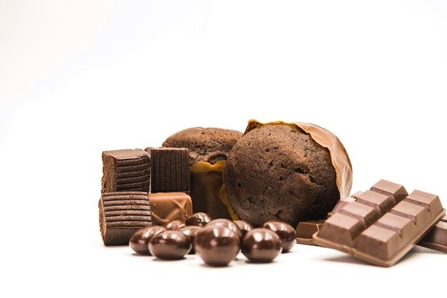 Magdalenas; barra de chocolate y bolas sobre fondo blanco Foto gratis